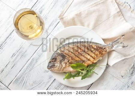 poster of Grilled gilt-head bream on the plate with wine
