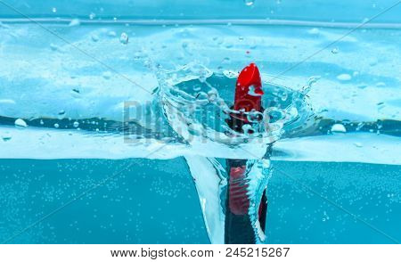 Water Resistant Red Lipstick Fall Into Pur, Transparent Water, Blue Background. Water Resistance Cos
