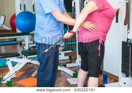 No Face Elderly Woman Doing Active, Special Exercises Guided By Physical Therapist At The Hospital R