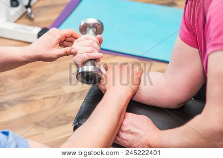 No Face Elderly Woman Doing Active, Working With Dumbbell Guided By Physical Therapist At The Hospit