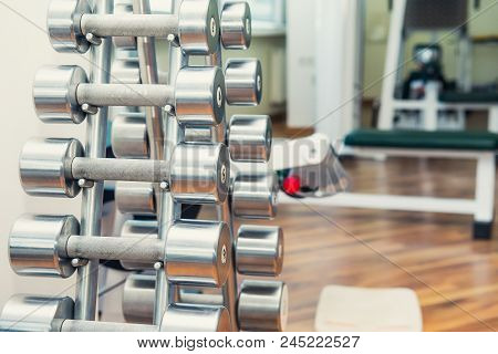 Rows Of Metal Heavy Dumbbells On Stand In Sport Gym, Physiotherapy Clinic. Physical Therapy Center.