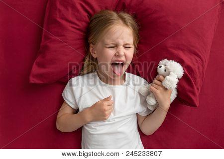 Capricious little girl resisiting bedtime poster