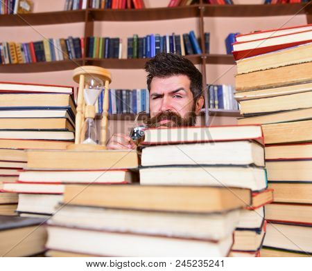 Man, Scientist Peeking Out Of Books. Teacher Or Student With Beard Studying In Library. Man On Serio