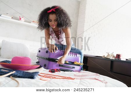 Worried Young Black Woman Packing Bags For Holiday. Girl Trying To Close Full Suitcase For Vacation,