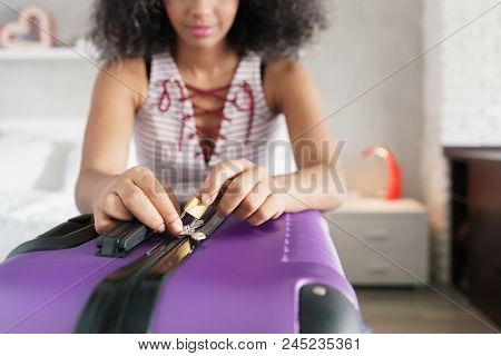 Young Black Woman Packing And Locking Bag For Holidays. Latino Girl Preparing Padlock For Travel Sui