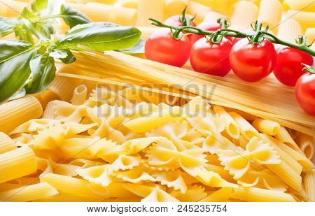 Heap Of Various Pasta With Tomato And Basil