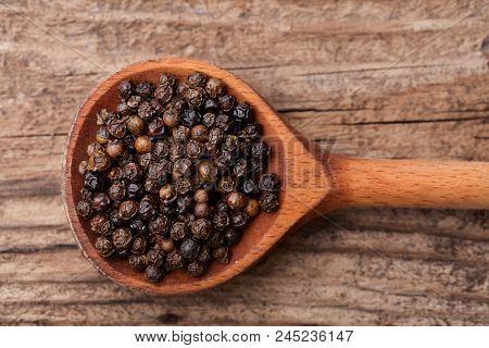Heap Of Black Peppercorns In Wooden Scoop On Wooden Bakcground