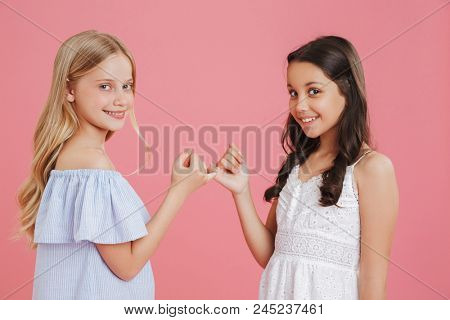 Photo of lovely little girls 8-10 years old wearing dresses hook each other's little fingers in conciliation or friendship isolated over pink background