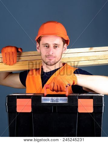 Man In Helmet, Hard Hat Holds Toolbox And Wooden Beams, Grey Background. Professional Woodworker Con