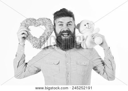 Bearded Man Holds Symbols Of Love. Hipster With Heart, Teddy Bear And Happy Joyful Face. Macho With