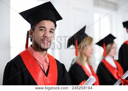Student in bachelor robe with diploma indoors. Graduation day