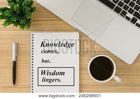 Notebook With Motivational And Inspirational Wisdom Quote On Wood Desk. Knowledge Comes But Wisdom L