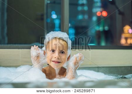 Happy Little Baby Boy Sitting In Bath Tub In The Evening Before Going To Sleep On The Background Of