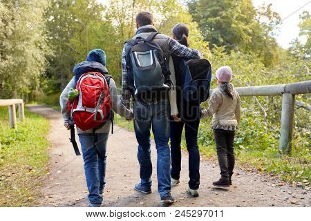 family, tourism and hiking concept - happy mother, father, son and daughter with backpacks walking in woods