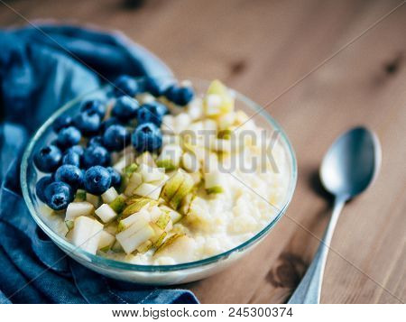 Bowl With Millet Porridge On Wooden Table Background. Organic Millet Porridge With Blueberry And Pea
