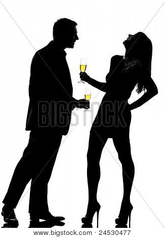 one caucasian couple man and woman driking flirting in studio silhouette isolated on white background