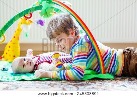 Happy Little Kid Boy With Newborn Baby Girl, Cute Sister. Siblings. Brother And Baby Playing With Co