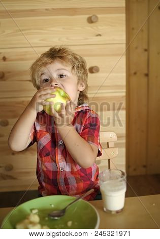 Baby Eats An Apple In A Village Hut. Breakfast, Morning, Family. Small Boy Child Eat Banana And Drin