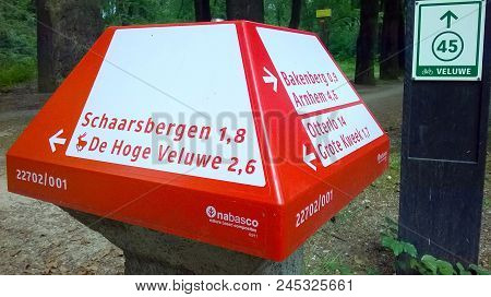 Arnhem, The Netherlands - June 12, 2018: Red Dutch Anwb Bicycle Signpost For Bike Paths And A Green