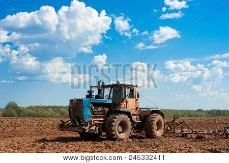 Tractor Plowing A Field On A Sunny Day. Preparing Land For Sowing. Agricultural Works At Farmlands.