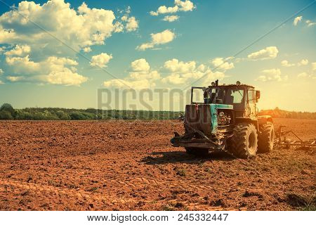 Tractor Plowing A Field At Sunset. Preparing Land For Sowing. Agricultural Works At Farmlands. Agric