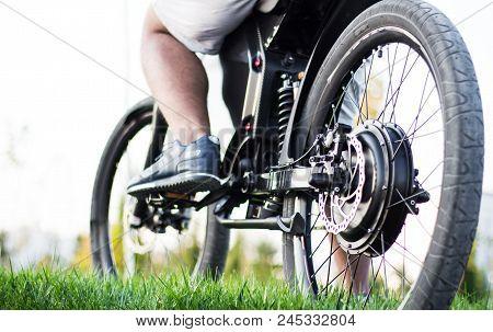 Man Biker Sitting On Electric Bike. Ebike Bicycle Environmentally Friendly Eco E-mountainbike Transp