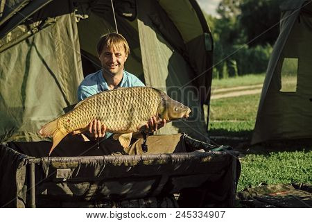 Fisherman With A Trophy. Carp Fishing, Angling, Fish Catching. Carp Trophy, Success, Achievement In