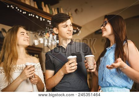 Young Man And Women With Paper Cups Standing At Bar Counter In Cafe, Laughing And Talking. Group Of