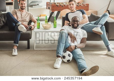Young Black Man Sitting On Rug With Ball Between Two Friends Playing Video Game With Joysticks In Ha