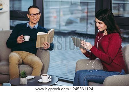 Smiling Man Reading Book And Holding Cup Of Coffee While Woman Using Digital Tablet