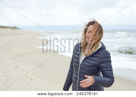 Smiling Woman On A Windy Deserted Beach Laughing As The Breeze Blows Her Hair Across Her Face, With
