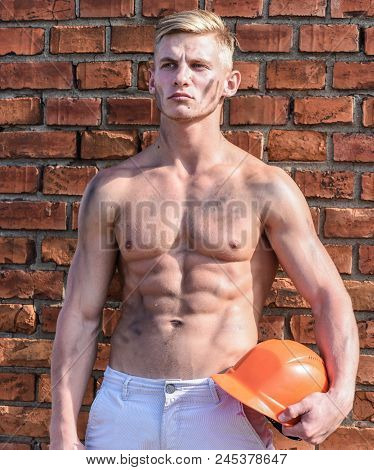 Builder With Muscular Torso And Helmet, Brick Wall Background. Athlete With Sexy Nude Torso With Har