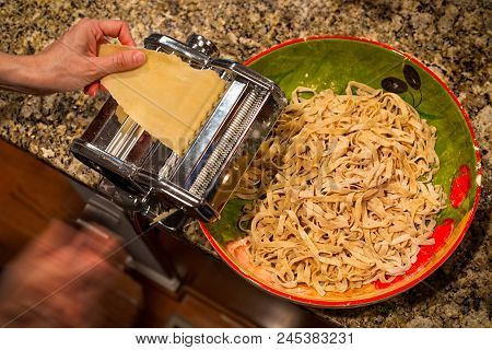 A Pasta Maker Cranking Out Homemade Fettucine In To A Bowl.