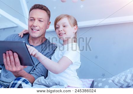 Innovative Generation. Low Angle Shot Of A Little Girl Touching A Screen Of Her Daddy Digital Tablet