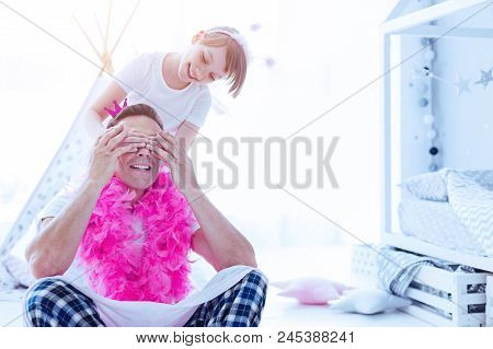 Guess Who. Smiling Preteen Daughter Closing Eyes Of Her Thoughtful Daddy Wearing A Bright Feather Bo
