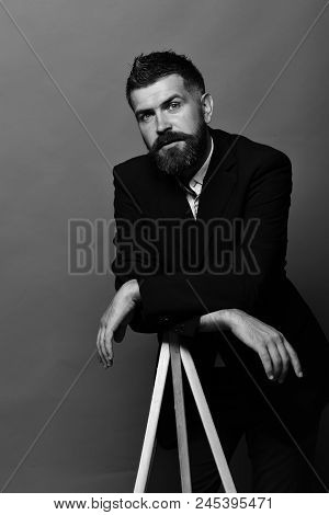 Macho Man Leans On Photo Tripod On Red Background. Man With Beard Wearing Classic Suit. Photography