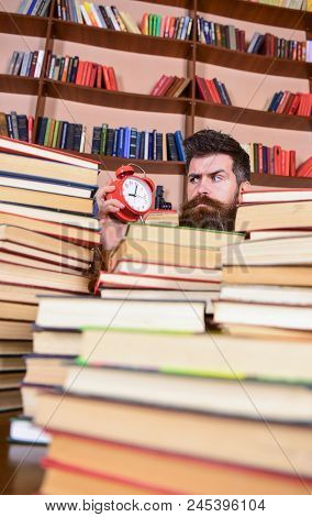 Deadline Concept. Man On Strict Face Looking At Clock, Bookshelves On Background. Teacher Or Student