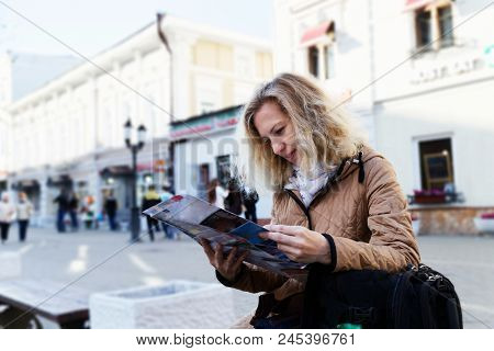 Woman Tourist Holding A Tourist Map Against Blurred Background. Tourist In Russia Discovering And Ex