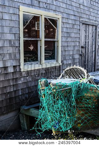An Artsy Reflection Of A Red Cottage In The Window Of A Gray Cottage In The Village Of Peggys Cove I