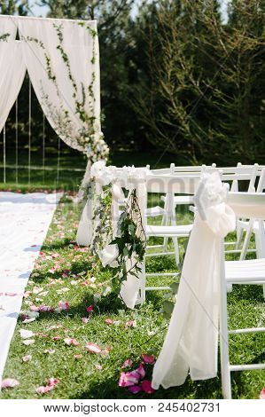 Beautiful Setting For Outdoors Wedding Ceremony Waiting For Bride And Groom And Guests. White Chairs