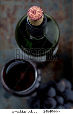Top View Of Red Wine Bottle. Macro, Selective Focus On Wine Cork. Wine Bottle, Glass And Grape On Vi