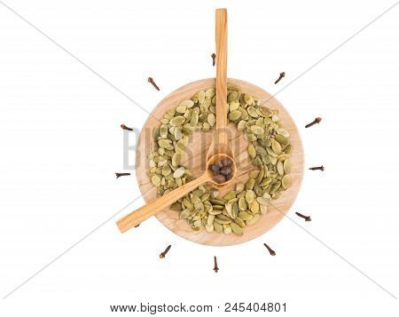 Two Wooden Spoons With Cloves And Seeds, Lying On The Wooden Board That Looks Like Round Clock With