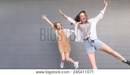 Funny Gay Girls Jumping Against The Background Of A Gray Dark Wall. Two Happy Girls In Stylish Light