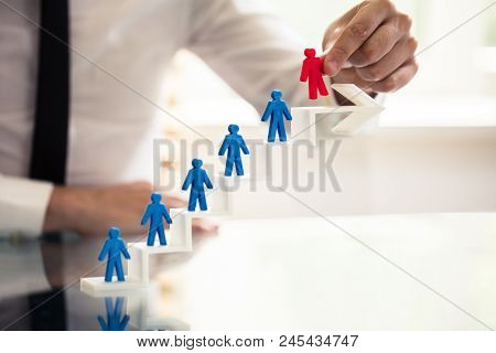 Businessperson Picking Red Human Figure From Staircase Made Of Arrow