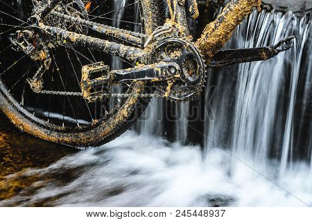 Dirty Mountain Bike Stands In A Creek Against The Small Waterfall. Dirty Chain Drive Mountain Bike C