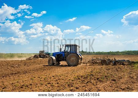 Two Tractors With A Plow In A Field On A Sunny Day. Preparing Land For Sowing. Agricultural Works At