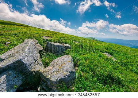 Lovely Summer Landscape. Grassy Hillside With Rocky Formations. Cloud Behind The Mountain Peak In Th
