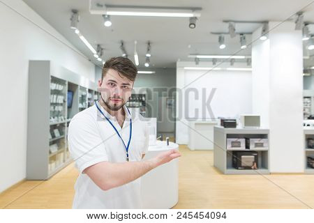 Handsome Man Consultant In A White T-shirt Invites You To The Electronics Store. Portrait Of A Conce