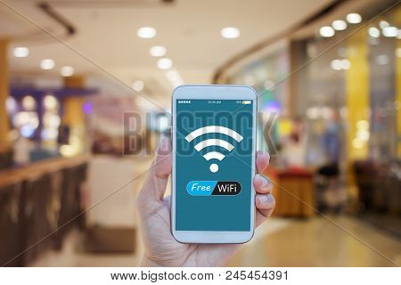 Hand Holding Smartphone With Free Wifi On Screen Over Blurred In Shopping Mall Background