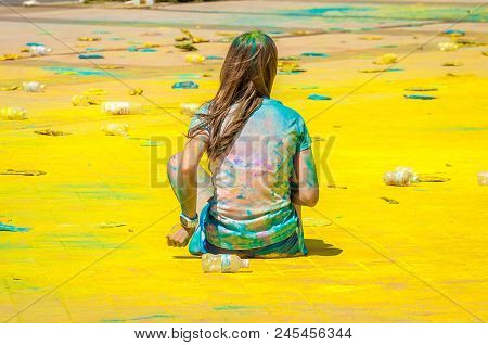 Holi's holiday is over. A lot of trash. The territory is covered with colored powders and scattered plastic bottles used. The girl is sitting in this garbage. Probably meditating Environmental concept.